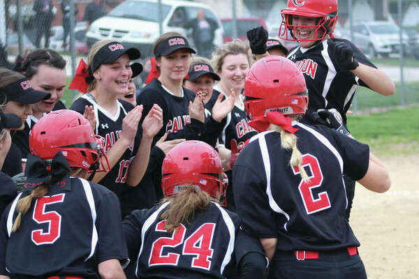 Sydney Baalman (right) is greeted by her Calhoun teammates at home plate after hitting a grand slam in the third inning to give the Warriors a 4-2 lead. The Tigers would answer with a 10-run inning in the fourth on their way to a 14-6 victory Monday in Hardin.