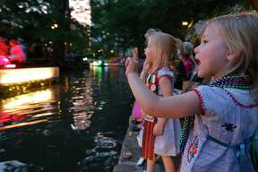 "Riley Steger (left) and her twin sister Brenna Steger watch the 2018 Texas Cavaliers River Parade ""Magnificent Missions"" held Monday April 23, 2018."