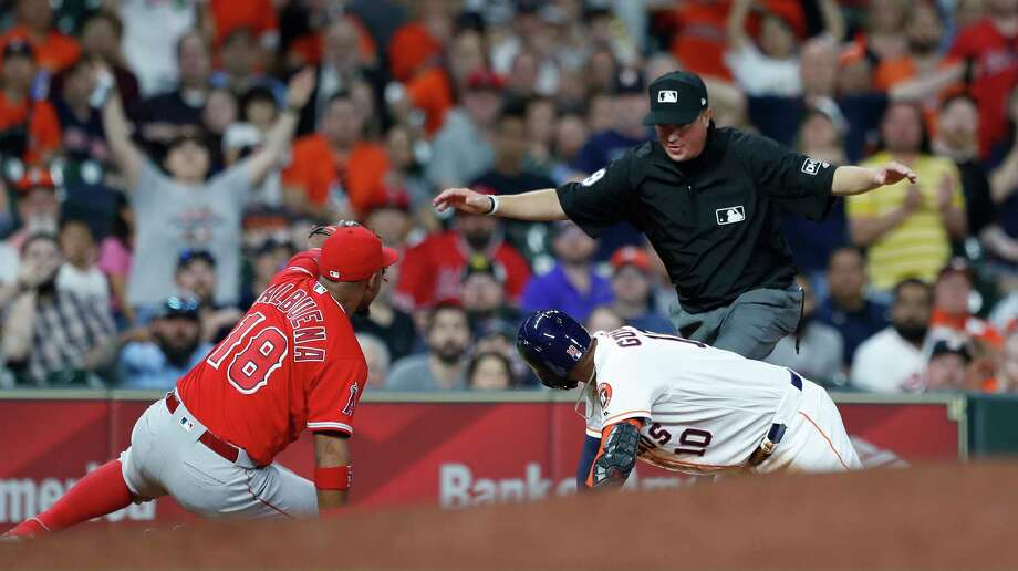 Houston Astros Yuli Gurriel (10) is called safe at thrid by umpire Cory Blaser as Los Angeles Angels third baseman Luis Valbuena (18) raises his glove but the call was overturned to end the game. Photo: Karen Warren, Houston Chronicle / © 2018 Houston Chronicle