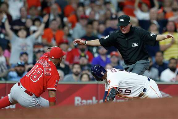 Houston Astros Yuli Gurriel (10) is called safe at thrid by umpire Cory Blaser as Los Angeles Angels third baseman Luis Valbuena (18) raises his glove during the ninth inning of an MLB game at Minute Maid Park, Monday, April 23, 2018, in Houston.