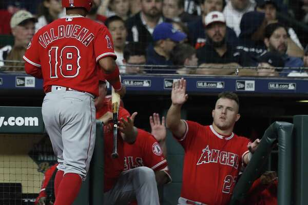 Former Astro Luis Valbuena is greeted by Mike Trout, right, after returning to the Angels' dugout in the fifth inning with Monday night's first run.