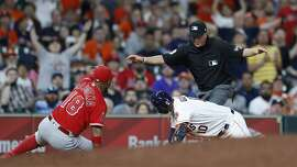 Houston Astros Yuli Gurriel (10) is called safe at thrid by umpire Cory Blaser as Los Angeles Angels third baseman Luis Valbuena (18) raises his glove during the ninth inning of an MLB game at Minute Maid Park, Monday, April 23, 2018, in Houston. ( Karen Warren  / Houston Chronicle )