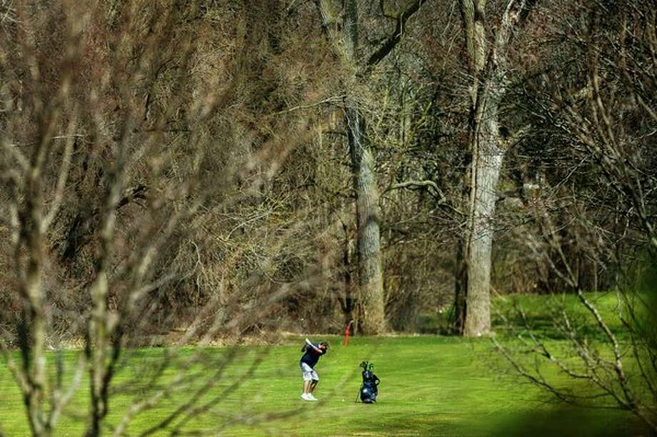 A man swings from the fairway on Monday afternoon at Currie Golf Course. Temperatures in Midland reached at least 67 degrees on what was forecast to be the warmest day of the week. (Katy Kildee/kkildee@mdn.net)