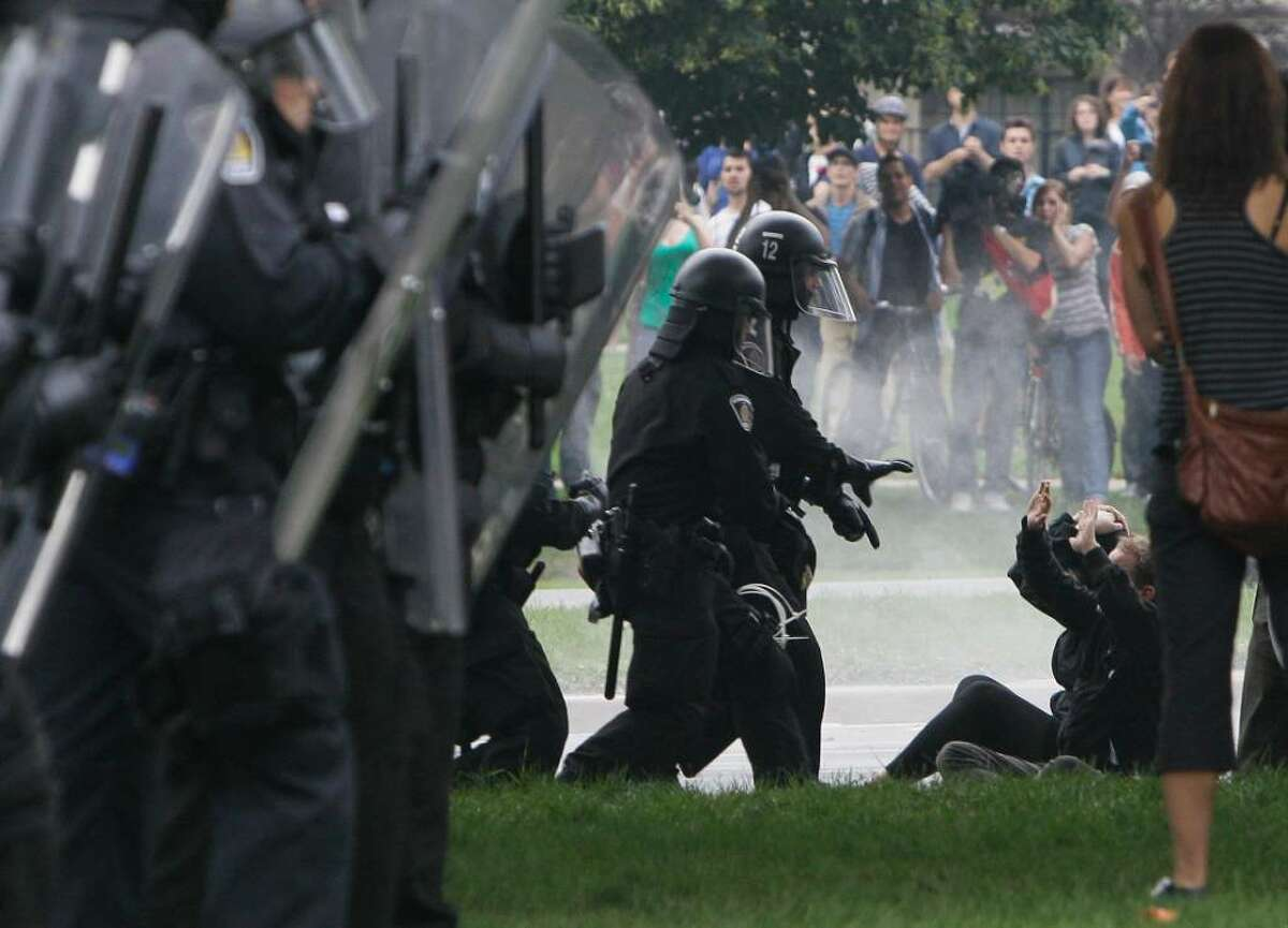 Riot police order some demonstrators to the ground and arrest them in Queens Park, Toronto, Saturday, June 26, 2010, as the G20 Summit gets underway. (AP Photo/Gerry Broome)