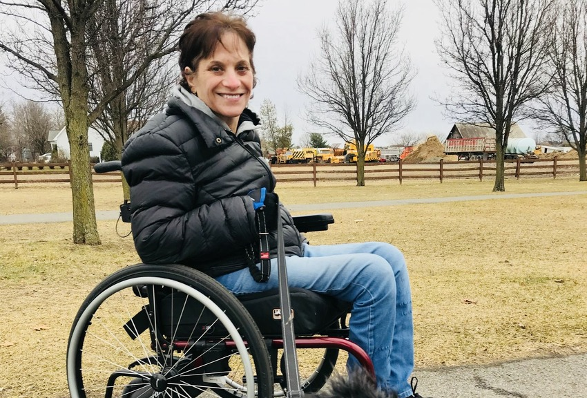Nancy Ladd-Butz, who was severely injured and paralyzed by a falling boulder at Thacher Park last summer, is seen in her wheelchair at The Crossings in Colonie with her dog, Leo (Provided photo)