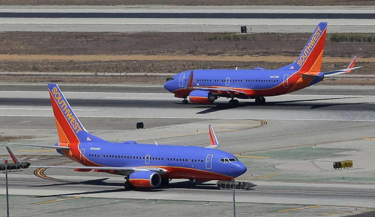 FILE - In this Sept. 4, 2013 file photo, a Southwest Airlines Boeing 737 takes off, rear, as another taxis in the north runway complex at Los Angeles International Airport (LAX). Average fares are rising on Southwest Airlines Co., the fuel bill is shrinking, and profit is soaring.The airline is gearing up for the holiday travel season, and officials say that bookings for November and December are strong. (AP Photo/Reed Saxon, File)
