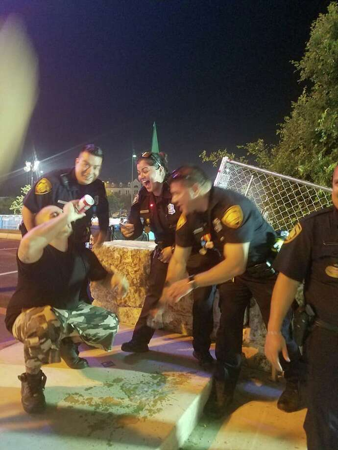 Facebook user Flawz Don Rodriguez snapped a picture of his friend Jose Garza chugging a beer while surrounded by laughing SAPD officers on Saturday. Photo: Courtesy,  Flawz Don Rodriguez