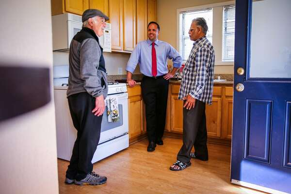 Realtor Michael Darling (center) chats with Ashok Patel (right)  and Joe Stangelini during an open house on 2nd Lane in South San Francisco, California, on Sunday, April 22, 2018.