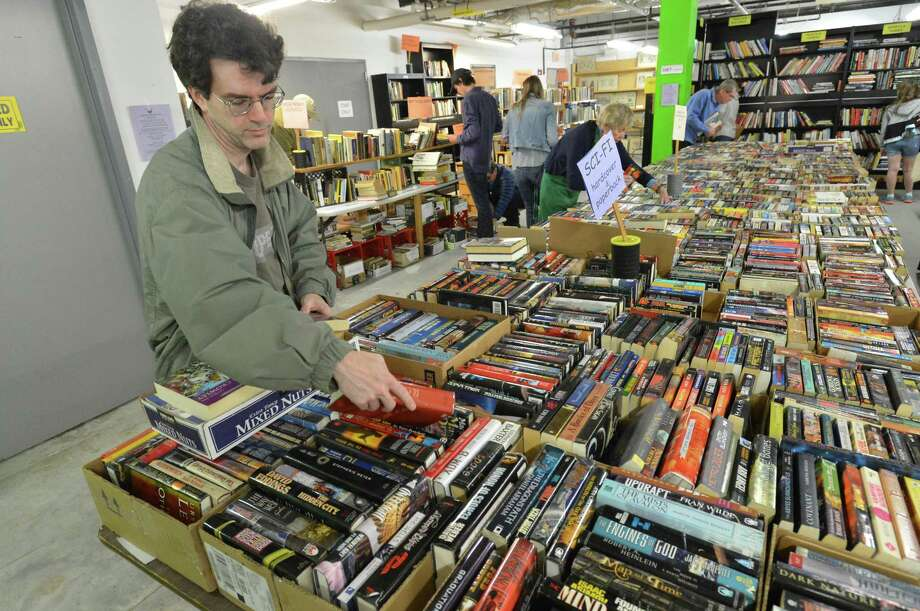 Michael Murphy from Fairfield picks out some hardcover books during the Wilton Library's Annual Gigantic Spring Book Sale Fundraiser on Sunday April 22, 2018 in Wilton Conn. Photo: Alex Von Kleydorff / Hearst Connecticut Media / Norwalk Hour