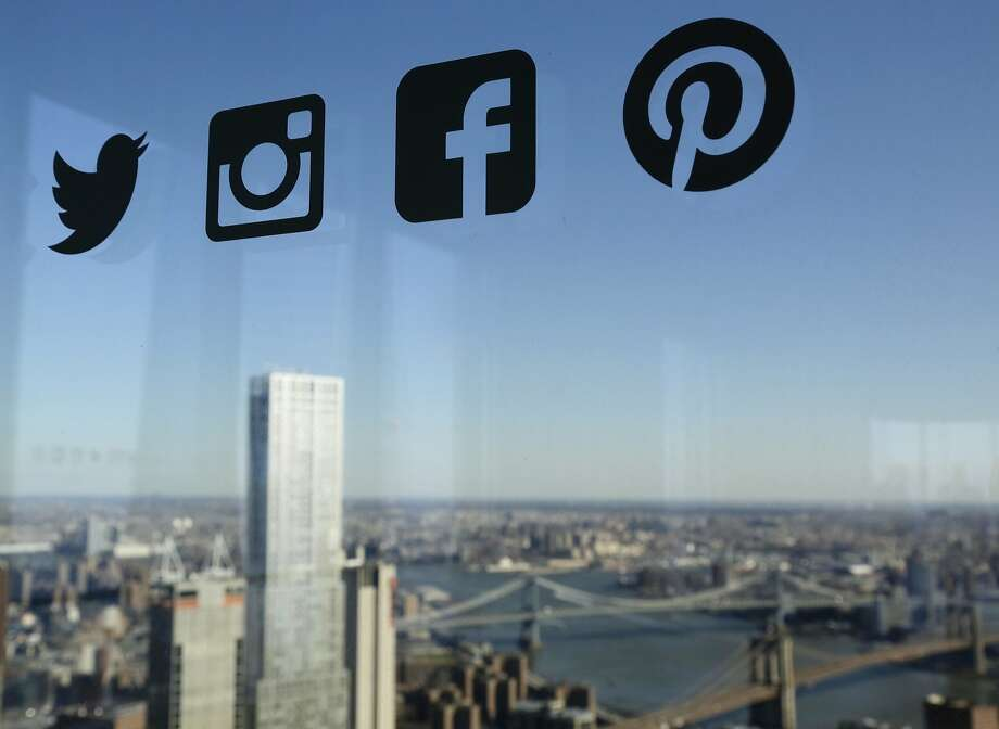Icons for Twitter, Instagram, Facebook and Pinterest are displayed on a window in New York. Only 9 percent of Americans don't use Facebook. Photo: Mark Lennihan / Associated Press 2016