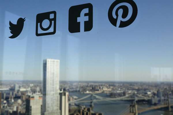 FILE- In this Jan. 13, 2016, file photo, Icons for Twitter, Instagram, Facebook and Pinterest are displayed on a window in New York. A new poll by the Associated Press-NORC Center for Public Affairs Research says 12 percent of Americans use Facebook �almost constantly,� while 34 percent use it several times a day. About 15 percent use it once a day, and only 9 percent of Americans don�t use Facebook. (AP Photo/Mark Lennihan, File)