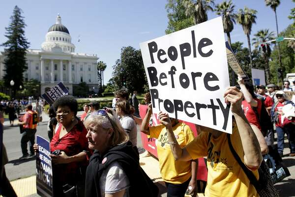 Supporters of a rent control initiative march near the Capitol calling for more rent control, Monday, April 23, 2018, in Sacramento, Calif. Backers of the initiative say they have collected enough signatures to allow voters to decide whether to repeal a 1995 law that restricts rent control. If certified by the secretary of state the initiative will appear on the November ballot. (AP Photo/Rich Pedroncelli)