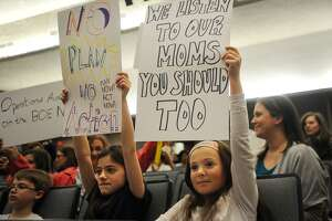 Stratford Academy students Josephine Mastro, 11, left, and Grace Miron-Dominguez, 9, protest their school being changed from a magnet to a regional school at the Stratford Board of Education meeting at Bunnell High School in Stratford, Conn. on Monday, April 23, 2018.