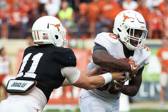 Sam Ehlinger (11) hands the ball off to Toneil Carter (30) during Texas' Orange-White spring NCAA college football game, Saturday, April 21, 2018, in Austin, Texas. (Ana Ramirez/Austin American-Statesman via AP)