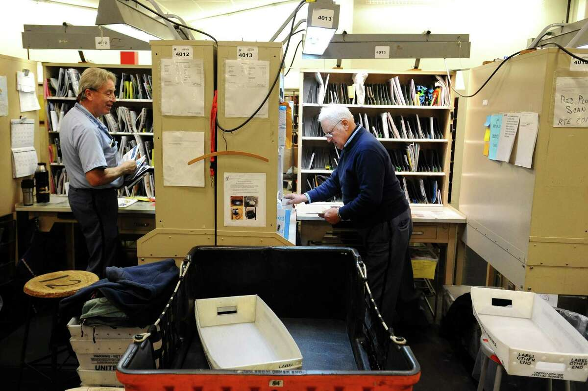 81-year-old Tony Spadaccini, right, sorts mail inside his cubicle at the Stamford Post Office on Camp Ave. before beginning his route through New Canaan in Stamford, Conn. on Tuesday, April 24, 2018. Spadaccini is celebrating his 60th year on the job.