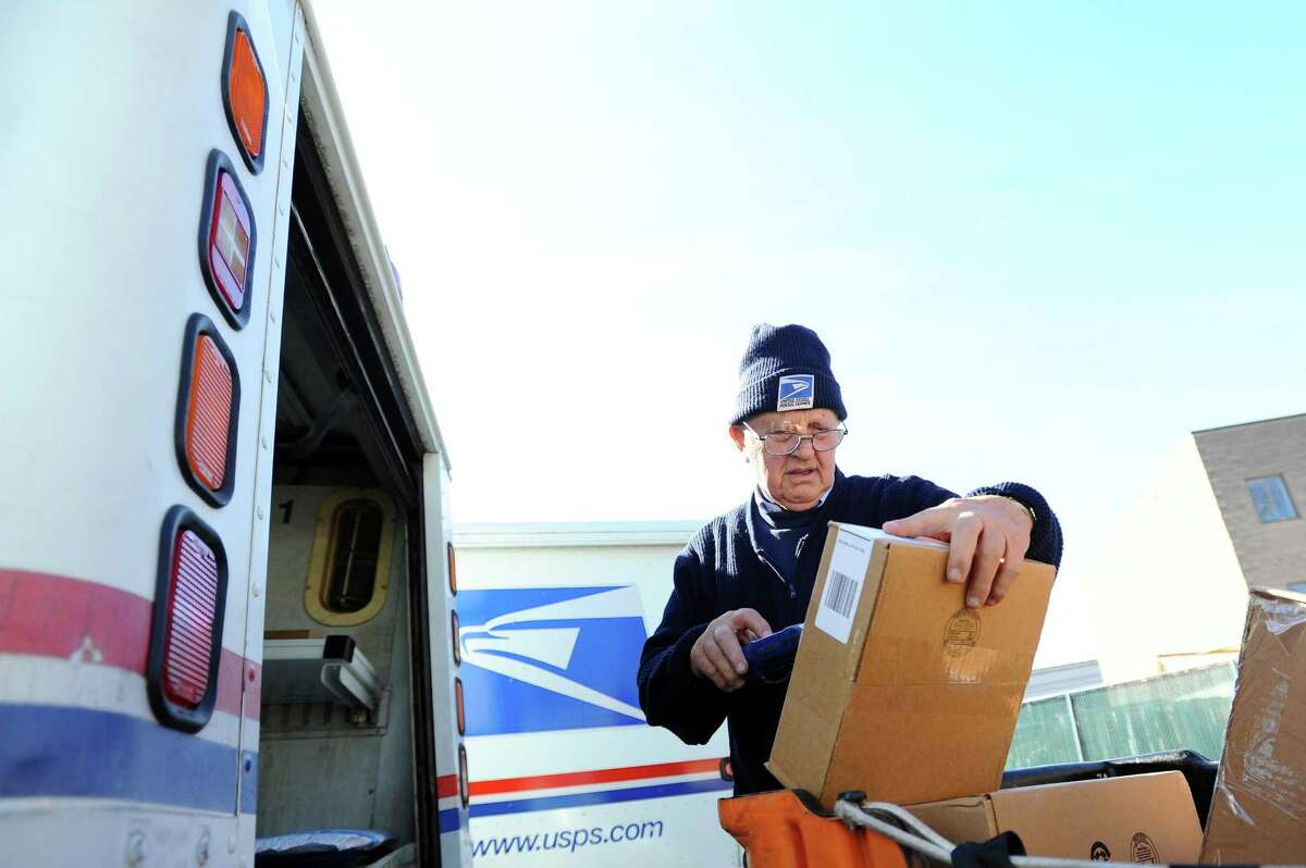 Tony Spadaccini, 81, scans a package before placing it in the back of his truck before beginning his route through New Canaan while at the Stamford Post Office on Camp Ave. in Stamford, Conn. on Tuesday, April 24, 2018. Spadaccini is celebrating his 60th year on the job.