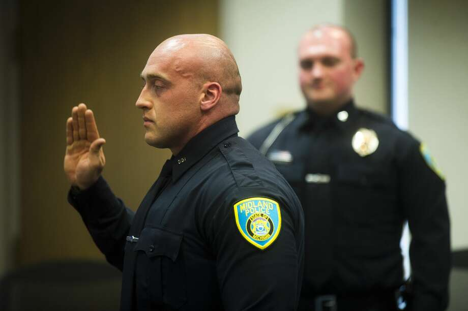 One of Midland Police Department's two newest officers, James Michael Compty, raises his hand while City Clerk Selina Tisdale reads an oath aloud during their officer swearing-in ceremony on Tuesday, April 24, 2018 at City Hall. (Katy Kildee/kkildee@mdn.net) Photo: (Katy Kildee/kkildee@mdn.net)