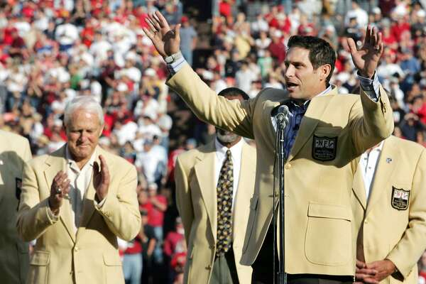 As his old coach Bill Walsh (L) claps, former San Francisco 49ers quarterback Steve Young talks to the crowd during a halftime ceremony where he received his NFL hall of fame ring in San Francisco, November 20, 2005. Young was honored for his recent induction into the NFL Hall of Fame. REUTERS/Lou Dematteis