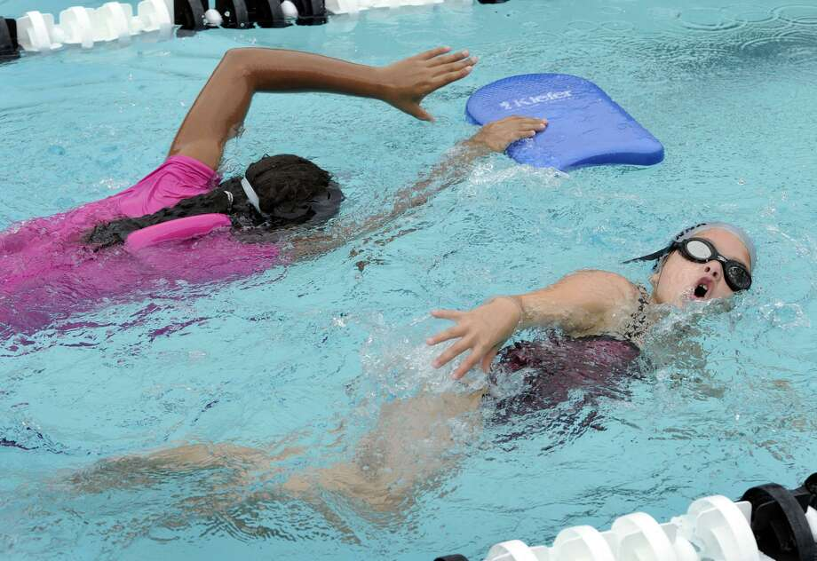 Searra Diggs, 11, of Danbury, left, and Arianna Petta, 7, of Brookfield, swim freestyle during the Western Connecticut YMCA Makos Swim Clinic, Tuesday, July 31, 2012. Photo: Carol Kaliff / Carol Kaliff / The News-Times