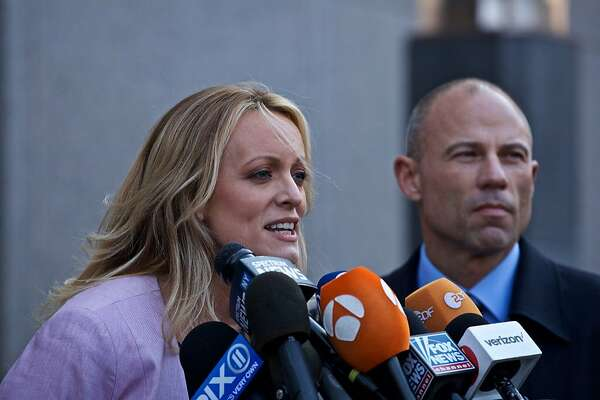 Adult-film actress Stormy Daniels, left, speaks to members of the media while attorney Michael Avenatti listens outside Federal Court in New York, U.S., on Monday, April 16, 2018. Daniels claims she had sex with Donald Trump in 2006 and took a $130,000 hush payment shortly before the 2016 election from lawyer Michael Cohen. Photographer: Victor J. Blue/Bloomberg