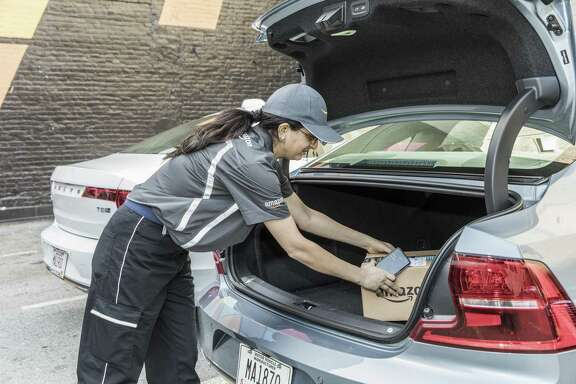 A worker demonstrates the delivery of an Amazon package to a vehicle's trunk in San Francisco, April 23, 2018. People in dozens of cities across the U.S. can soon start getting their Amazon orders delivered to a parked car, provided their vehicle has the proper technology.