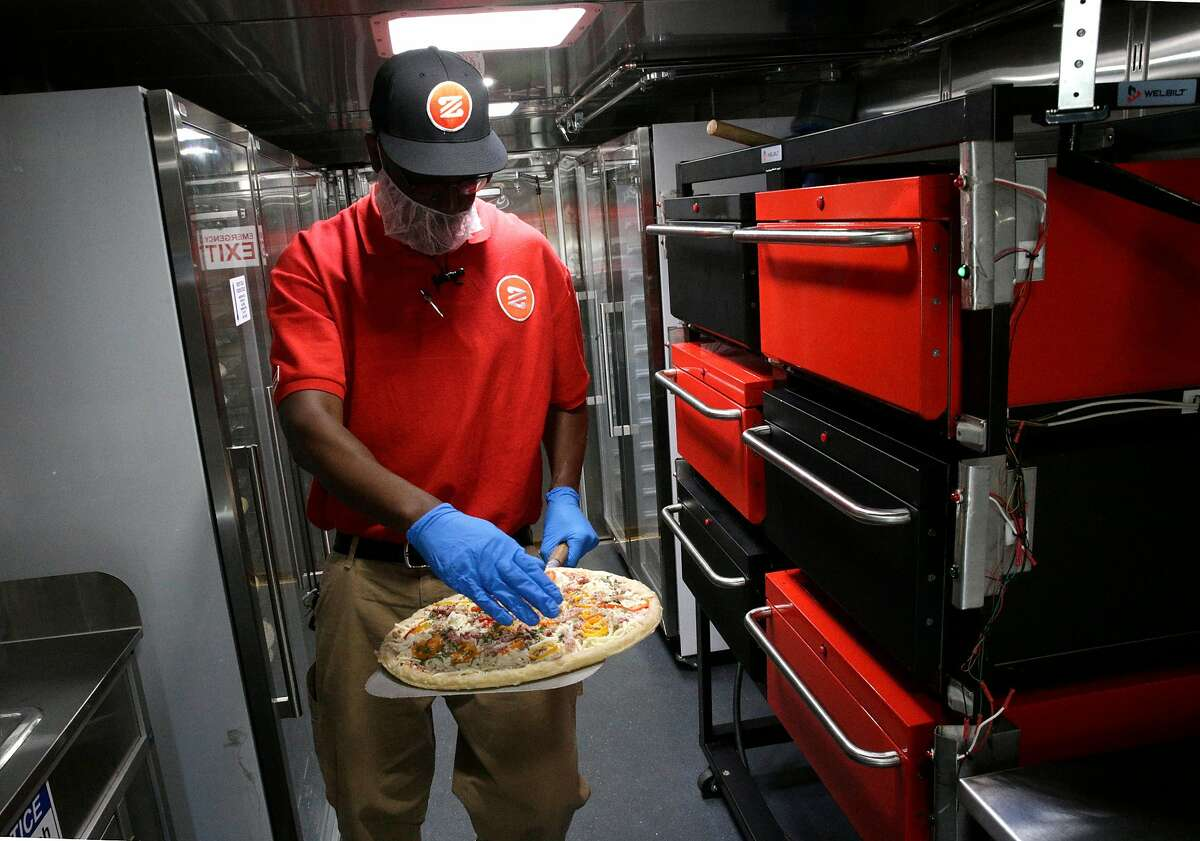 """Zume Captain Skylar Morris, the """"Pielot"""" of this truck crew, works inside the kitchen preparing pizzas while parked along El Camino Real in Palo Alto, Calif., Ca., on Tues. April 17, 2018. Zume Pizza uses robotic pizza-makers and smart ovens inside a truck to deliver cooked-to-order pizzas to customers."""