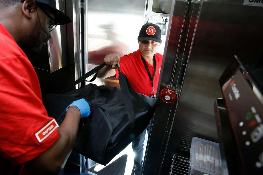 """Zume Captain Skylar Morris (left), the truck crew """"pielot,"""" hands a pizza for delivery to driver Deepak Dabadi. Photo: Photos By Michael Macor / The Chronicle"""