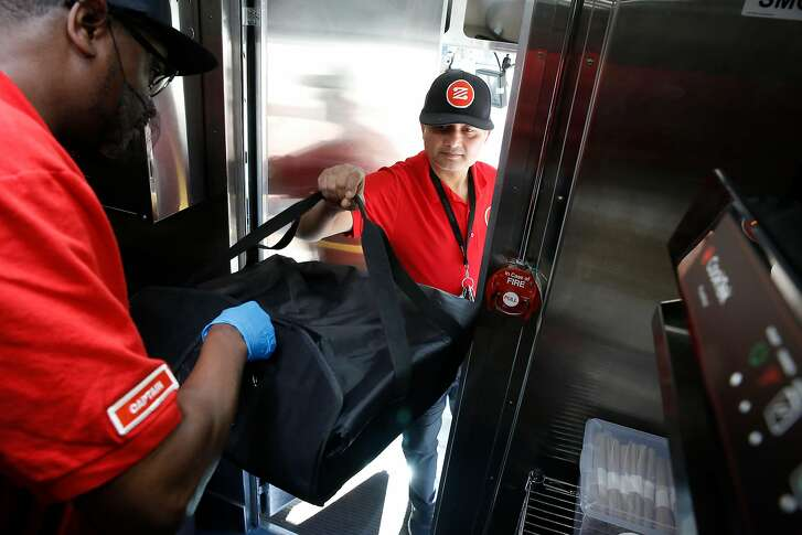 """Zume Captain Skylar Morris, ( left) the """"Pielot"""" of this truck crew hands off a pizza for delivery to driver Deepak Dabadi in Palo Alto, Calif., Ca., on Tues. April 17, 2018. Zume Pizza uses robotic pizza-makers and smart ovens inside a truck to deliver cooked-to-order pizzas to customers."""