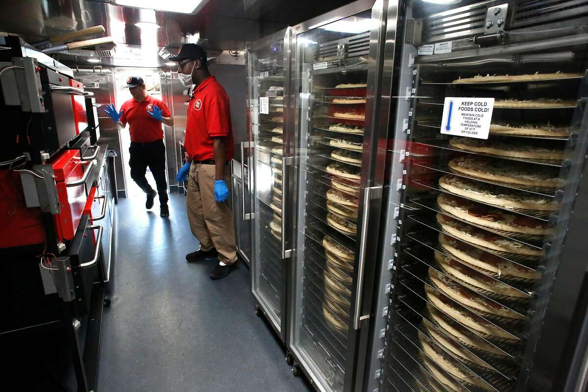 Zume employees Gustavo Vega, (left) and Skylar Morris inside the pizza kitchen truck with dozens of pizzas set for preparation, parked along El Camino Real in Palo Alto, Calif. on Tues. April 17, 2018. Zume Pizza uses robotic pizza-makers and smart ovens inside a truck to deliver cooked-to-order pizzas to customers.