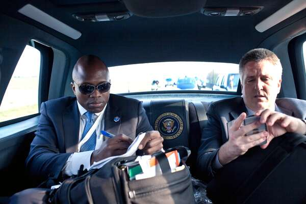 President Barack Obama's personal aide Reggie Love, left,  and White House physician Dr. Jeffrey Kuhlman check their notes as they travel in the Presidential motorcade April 4, 2009 in Strasbourg, France. White House Photo/Pete Souza