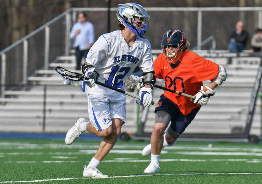 Brian Minicus (12) of the Darien Blue Wave sets up a play during a game against Manhassett (NY) at Darien High School on Saturday April 14, 2018, in Darien, Connecticut. Photo: Gregory Vasil / For Hearst Connecticut Media / Connecticut Post Freelance