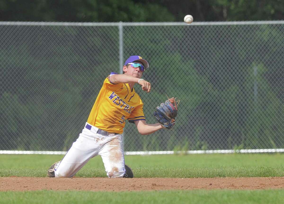 Westhill's TJ Wainwright throws from his knees to get an out against Trumbull in a 2017 game in Stamford.