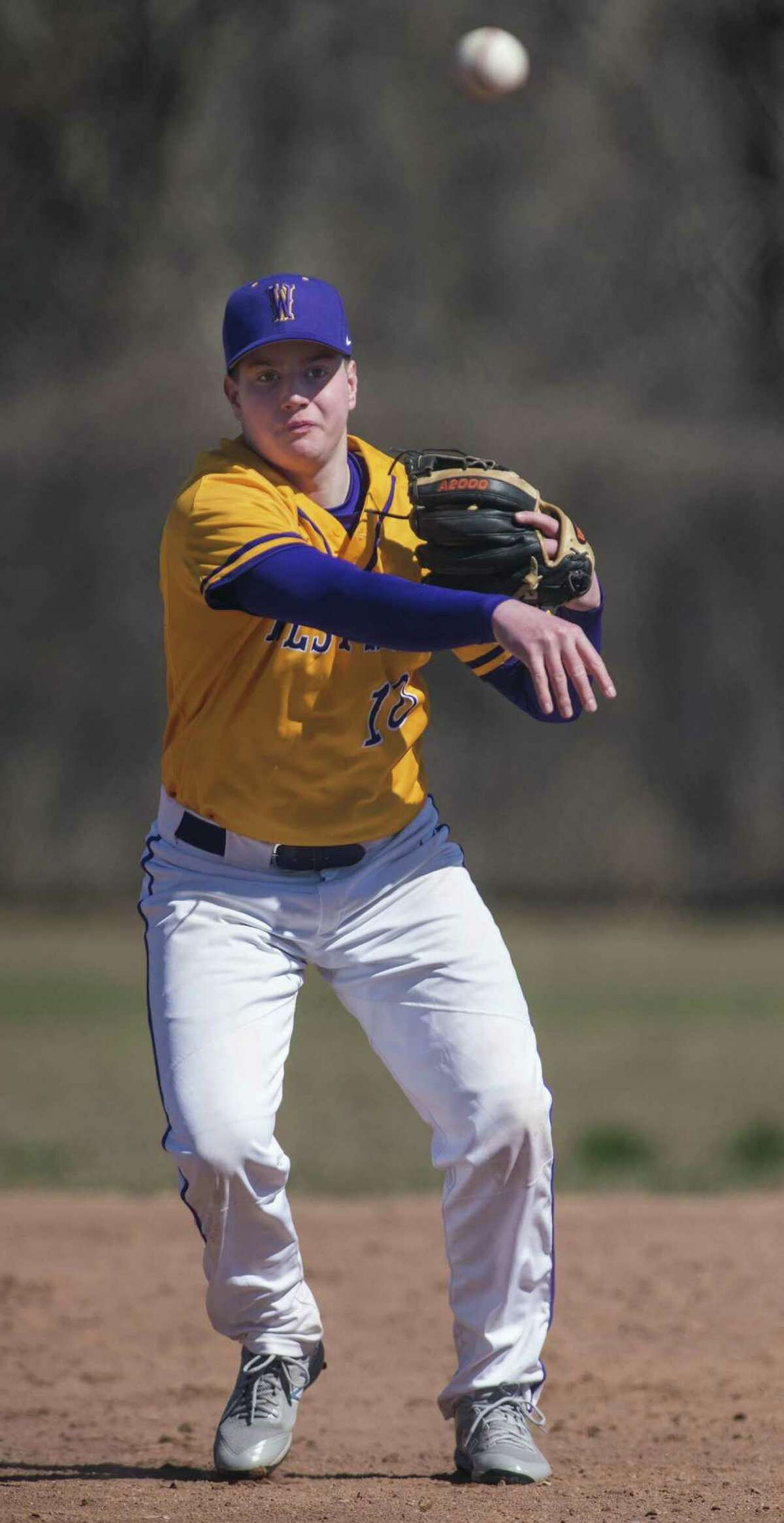 Westhill's Leo Socci throws to first during a March 31 game against Weston in Stamford.