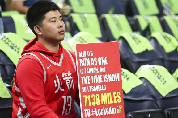 Meng-Han Yang, who traveled from Taiwan to see the Houston Rockets play, holds a sign behind the bench before the Rockets take on the Minnesota Timberwolves in Game 4 of the first round of the NBA Playoffs at Target Center Monday, April 23, 2018 in Minneapolis. (Michael Ciaglo / Houston Chronicle)
