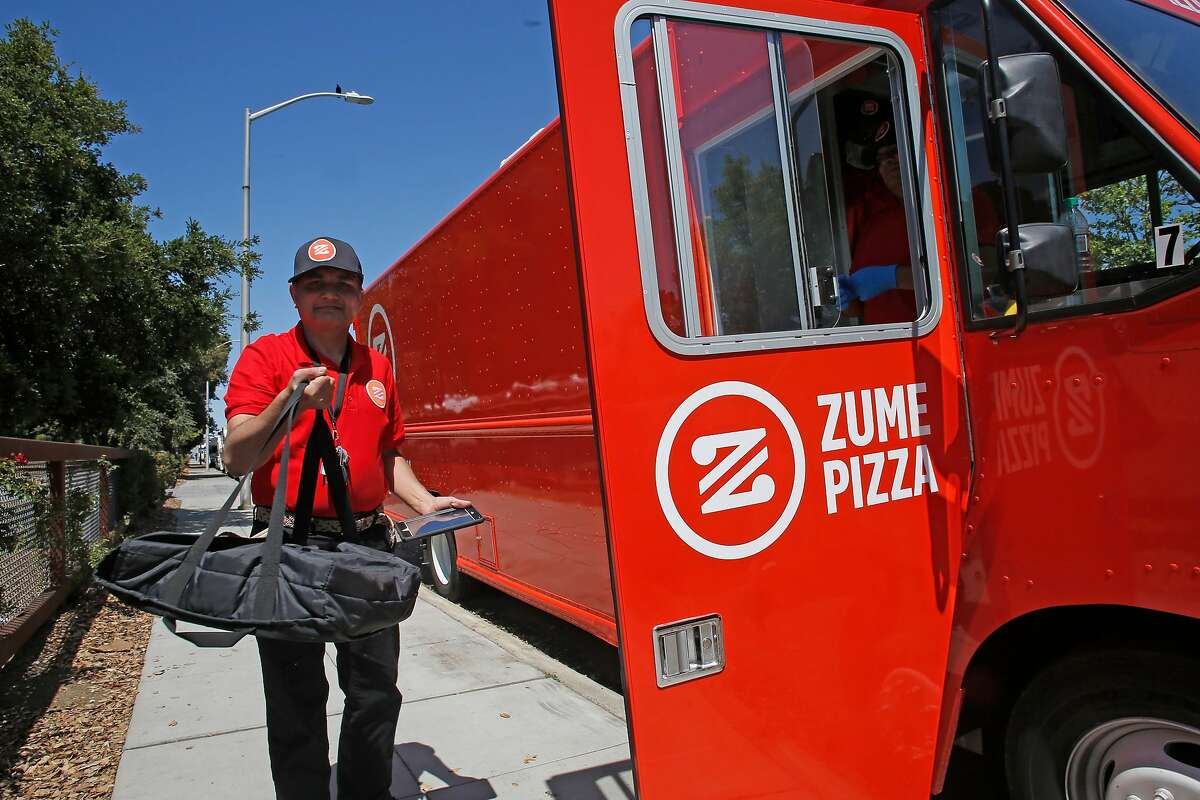 Zume driver Deepak Dabadi with a pizza in-hand for delivery from the Zume pizza truck parked along El Camino Real in Palo Alto, Calif., Ca., on Tues. April 17, 2018. Zume Pizza uses robotic pizza-makers and smart ovens inside a truck to deliver cooked-to-order pizzas to customers.