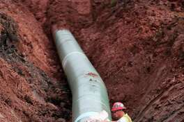 FILE - In this Aug. 21, 2017, file photo, a pipe fitter lays the finishing touches to the replacement of Enbridge Energy's Line 3 crude oil pipeline stretch in Superior, Minn. An administrative law judge is due to recommend whether Minnesota regulators should approve Enbridge Energy's proposal for replacing its aging Line 3 crude oil pipeline across northern Minnesota. The proposal has drawn strong opposition because the line would carry Canadian tar sands crude across environmentally sensitive areas in the Mississippi River headwaters region where American Indians harvest wild rice and hold treaty rights. (Richard Tsong-Taatarii/Star Tribune via AP, File)
