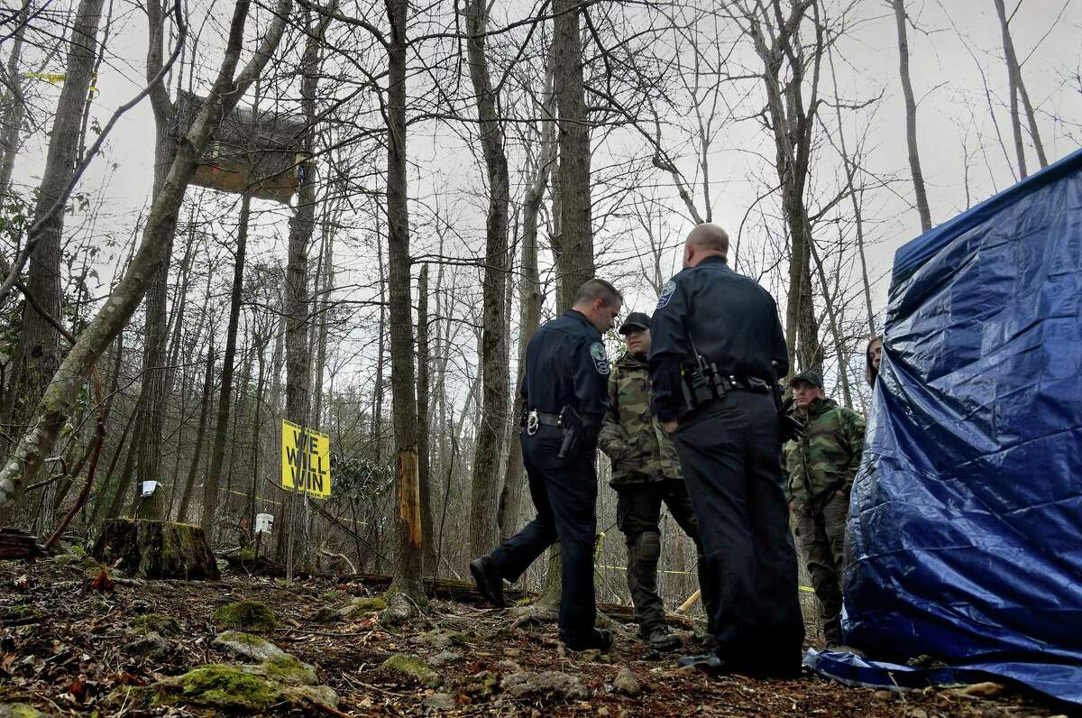 """State and local police, who are waiting to arrest Theresa """"Red"""" Terry, stand near her platform in Roanoke County, Virginia, where she is protesting the approach of the Mountain Valley Pipeline along with her daughter, Theresa Minor Terry. Must credit: Washington Post photo by Michael S. Williamson"""