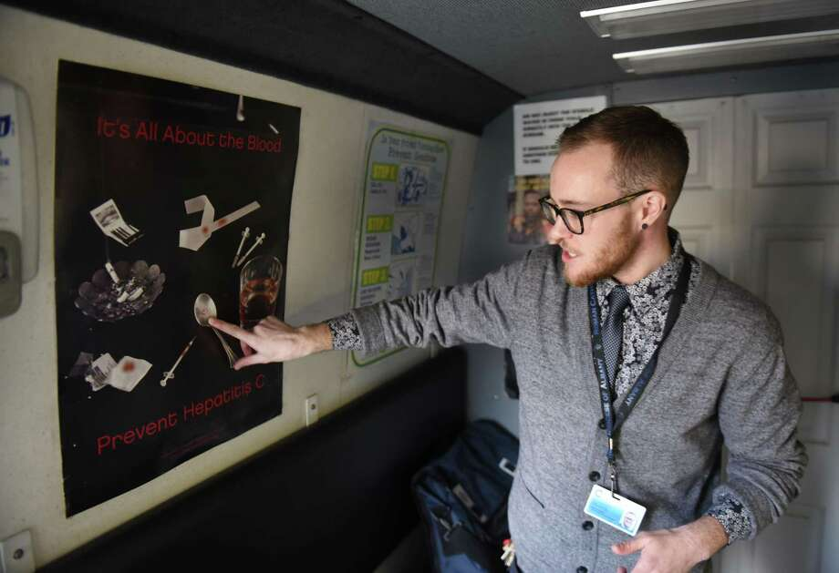 Luke Grandis, program coordinator at Project Safe Point, points to a poster in Safe Point's needle exchange van which shows lesser known ways that diseases, such as hepatitis C, can spread between IV drug users on April 11, 2018, in Albany N.Y. Bexar County officials are considering installing a needle exchange program here, but talks are in the early stage. Photo: Will Waldron /Albany Times Union / 20043482A