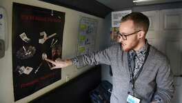 Luke Grandis, program coordinator at Project Safe Point, points to a poster in Safe Point's needle exchange van which shows lesser known ways that diseases, such as hepatitis C, can spread between IV drug users on April 11, 2018, in Albany N.Y. Bexar County officials are considering installing a needle exchange program here, but talks are in the early stage.
