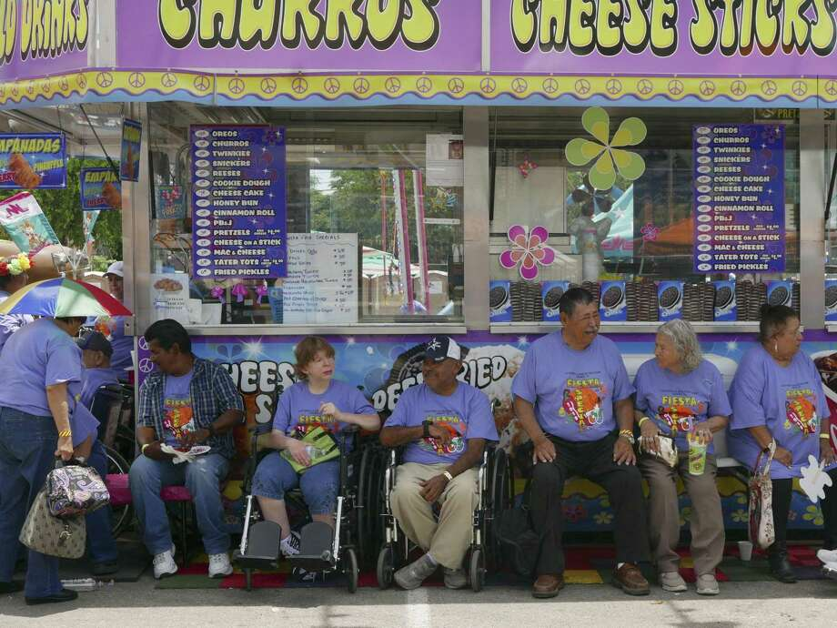 People from La Estrella Adult Day Care in Hondo enjoy a slice of shade during Fiesta Especial in the Alamodome parking lot on Tuesday, April 24 2018. The event offered unlimited carnival rides to adults and children with cognitive, developmental and physical disabilities. Photo: Billy Calzada, Staff / San Antonio Express-News / San Antonio Express-News