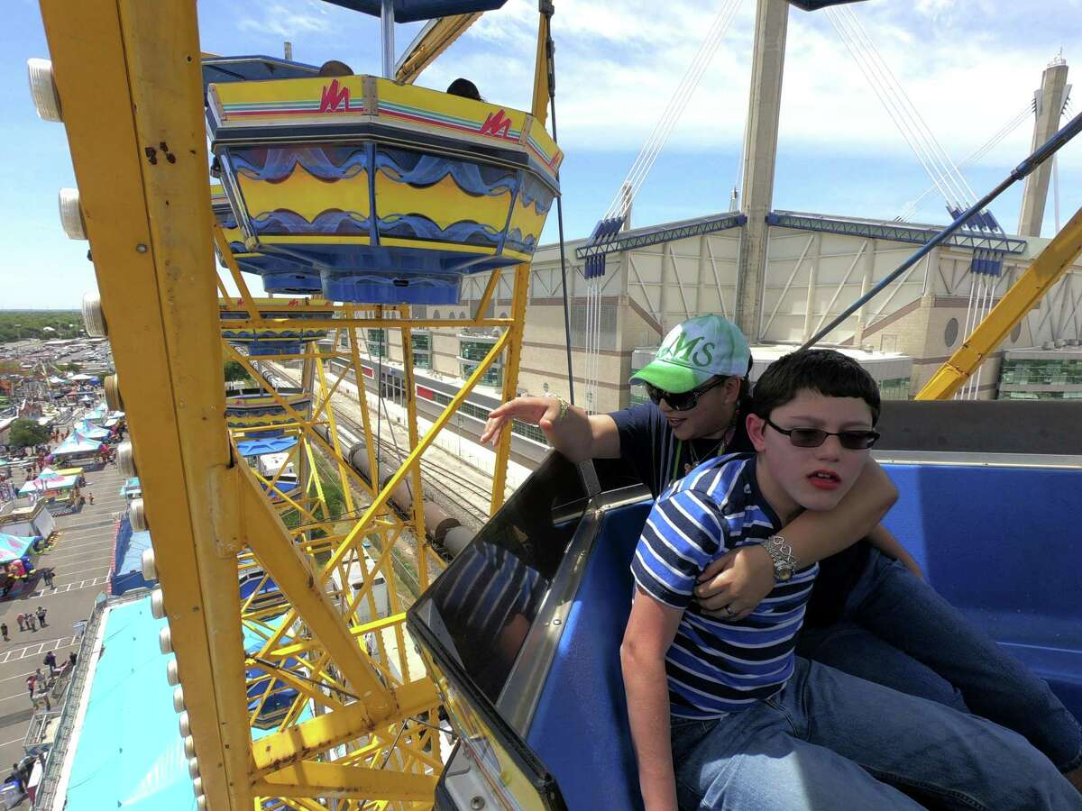 Miriam Plummer, who works with special needs children in the Judson Independent School District, encourages Dylan Schumann, 13, who has autism, as they ride the Wade Shows Ferris wheel during Fiesta Especial in the Alamodome parking lot on Tuesday, April 24 2018. The event offered unlimited carnival rides to adults and children with cognitive, developmental and physical disabilities.