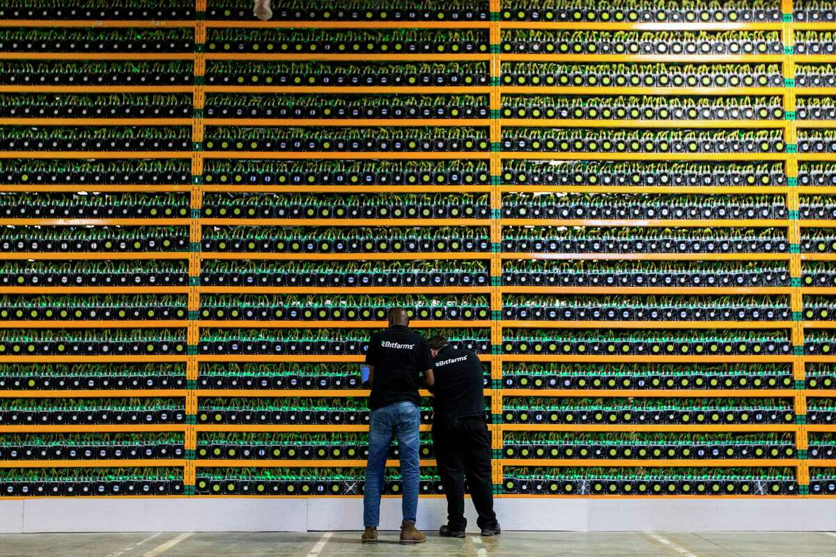 Technicians inspect Bitcoin mining at Bitfarms, Saint Hyacinthe, Quebec. Some cities have enacted or are considering bans. (Lars Hagberg / Getty Images)