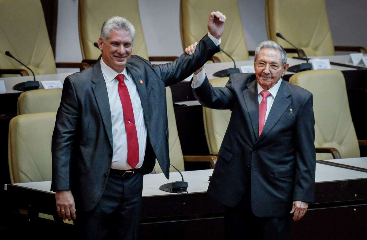 Outgoing Cuban President Raul Castro, right, raises the arm of Cuba's new President Miguel Diaz-Canel after he was formally named by the National Assembly, in Havana on April 19. Miguel Diaz-Canel succeeds Raul Castro - a historic handover ending six decades of rule by the Castro brothers. The 57-year-old Diaz-Canel, who was the only candidate for the presidency, was elected to a five-year term with 603 out of 604 possible votes in the National Assembly.