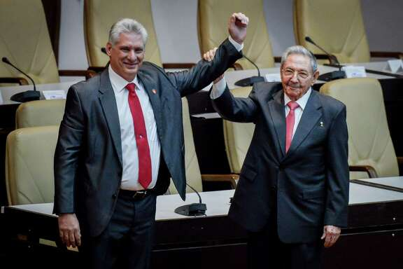 Outgoing Cuban President Raul Castro, right, raises the arm of Cuba's new President Miguel Diaz-Canel after he was formally named by the National Assembly, in Havana on April 19. Miguel Diaz-Canel succeeds Raul Castro — a historic handover ending six decades of rule by the Castro brothers. The 57-year-old Diaz-Canel, who was the only candidate for the presidency, was elected to a five-year term with 603 out of 604 possible votes in the National Assembly.