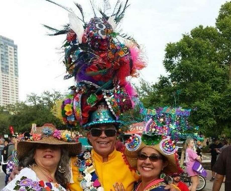 "Michael Quintanilla is pictured with two fans at Fiesta Fiesta, the Friday event where he led the ""People's Parade"" wearing his ""hat of hats"" stacked 11 hats tall, one for each day of Fiesta. Photo: Courtesy Photo"
