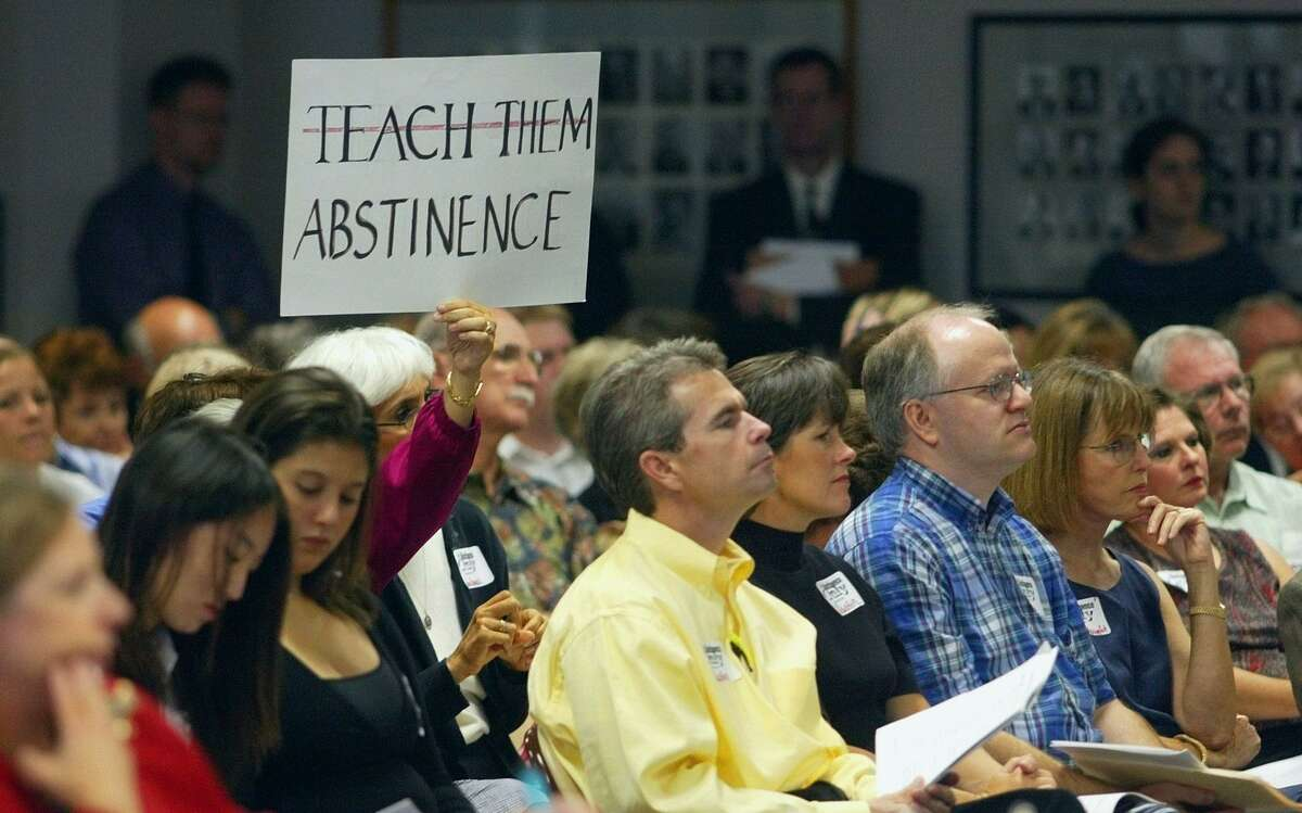 A woman holds a sign during a State Board of Education public hearing in 2004 in Austin on new health textbooks.