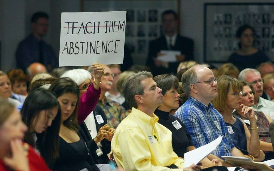 A woman holds a sign during a State Board of Education public hearing in 2004 in Austin on new health textbooks. Photo: HARRY CABLUCK, STF / AP / AP