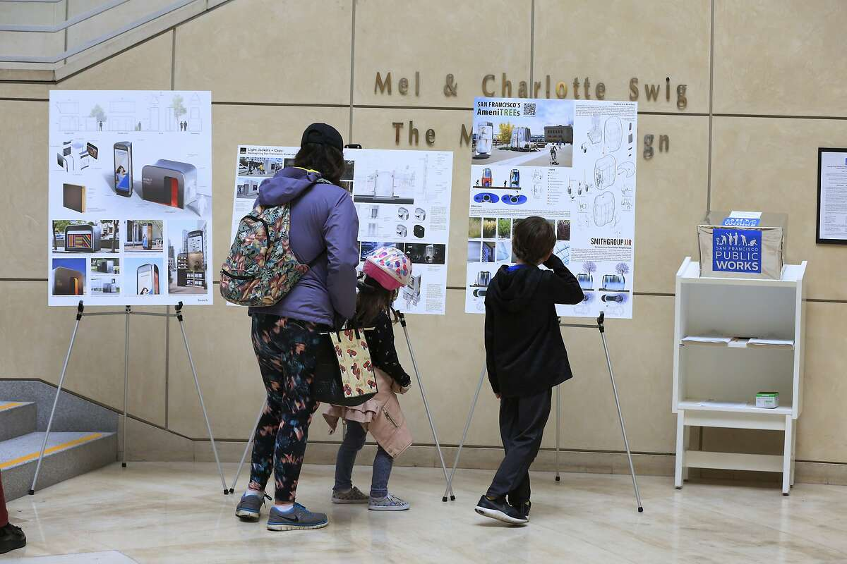 Anahi Palomares (l to r), Olive Franco, 5; and Judah Franco, 8, look over designs for replacement of San Francisco's on-street public toilets by three finalists at the main library in San Francisco, Calif., on Tuesday, April 24, 2018.