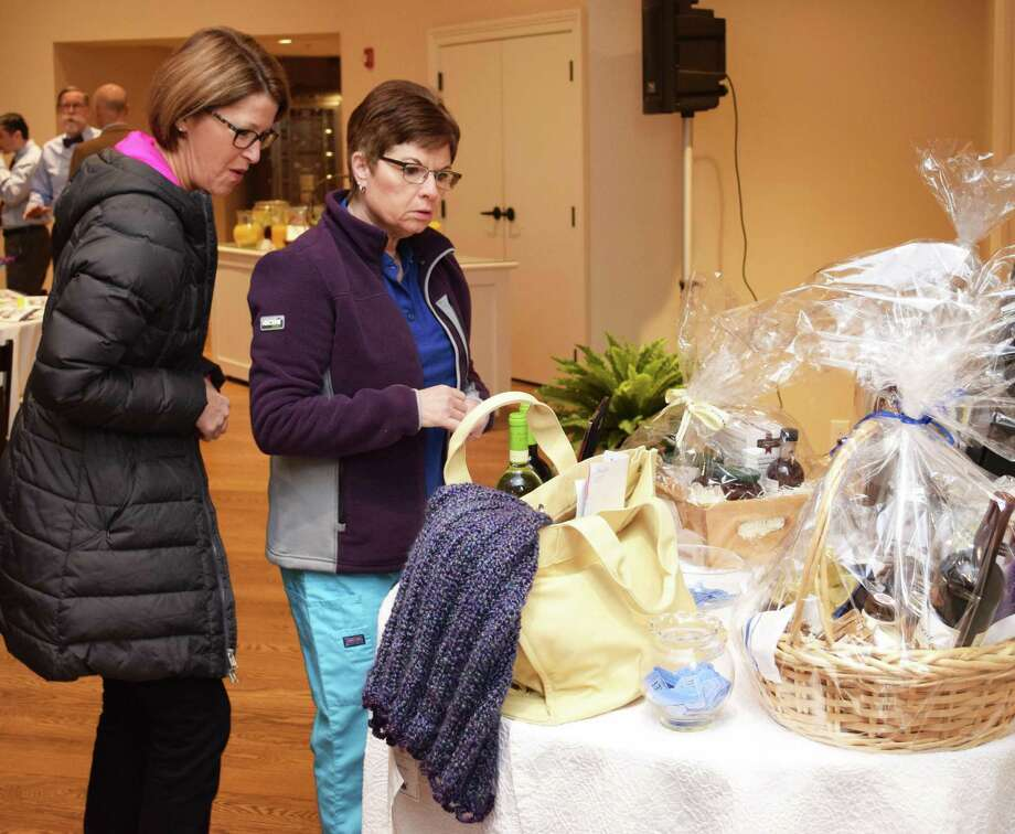 Guests of the NMVNA & Hospice's recent breakfast, Maureen Mester, left, and Marcy Corrigan look over the table of baskets with goods for a drawing. Photo: Deborah Rose / Hearst Connecticut Media / The News-Times  / Spectrum