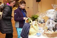 Guests of the NMVNA & Hospice's recent breakfast, Maureen Mester, left, and Marcy Corrigan look over the table of baskets with goods for a drawing.